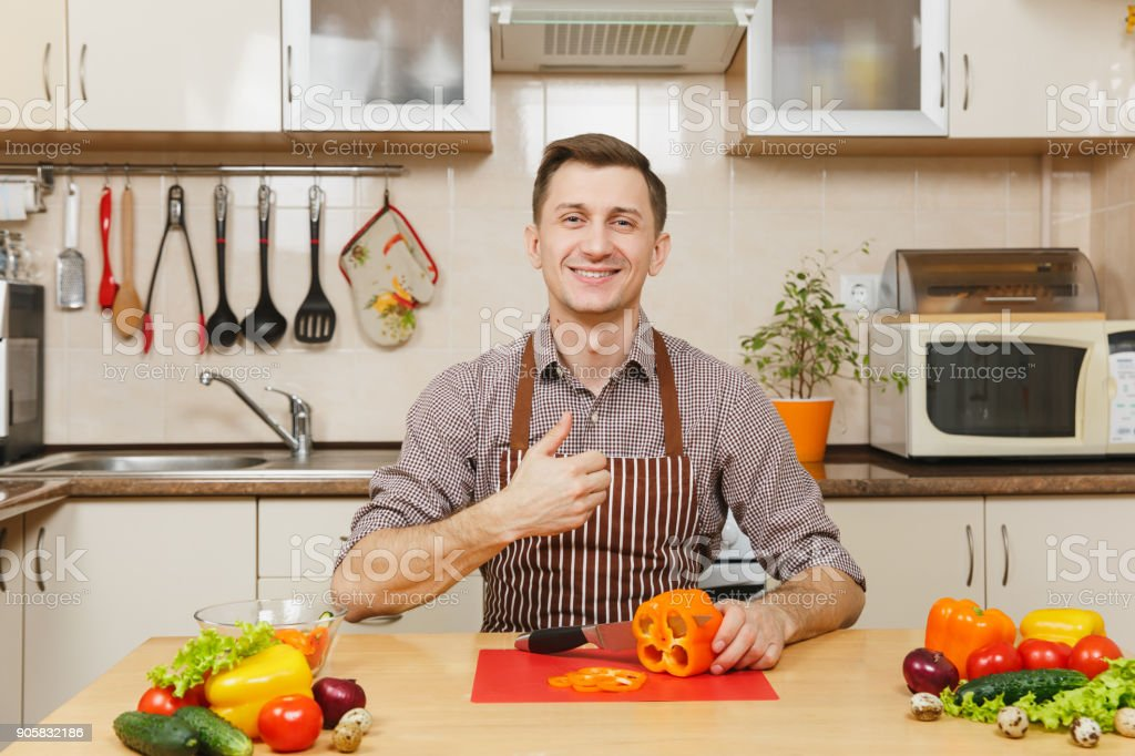 Handsome smiling caucasian young man in an apron, brown shirt sitting at table, showing thumb up, cuts vegetable for salad with knife in light kitchen. Dieting concept. Cooking at home. Prepare food. stock photo
