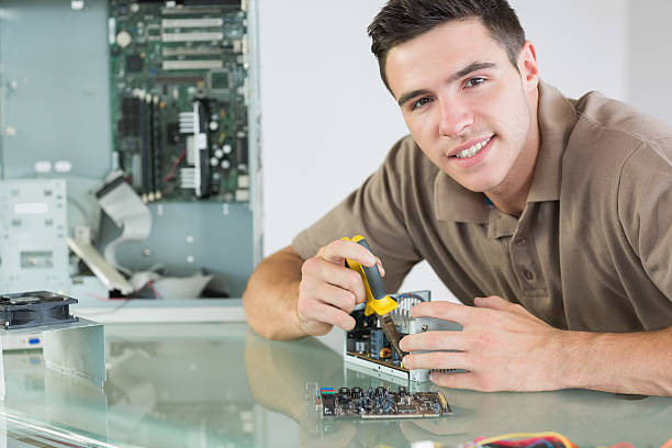 Handsome smiling computer engineer repairing hardware with pliers stock photo