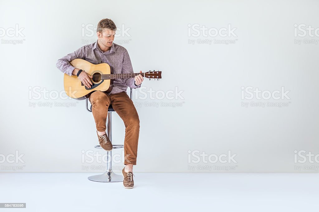Handsome smiling guitarist play music siting on chair stock photo