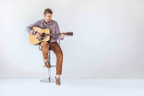 Handsome smiling guitarist play music siting on chair Handsome smiling guitarist play music siting on chair in studio with copy space guitarist stock pictures, royalty-free photos & images