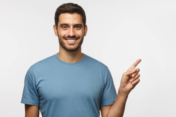 英俊的微笑的男性在藍色 t恤指向權利與手指查出在灰色背景 - 瞄準 個照片及圖片檔