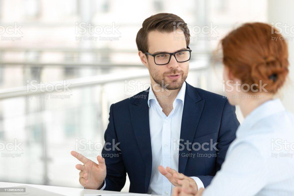 Hübsche lächelnde männliche Büroangestellte im Gespräch mit weiblicher Kollegin - Lizenzfrei Abmachung Stock-Foto