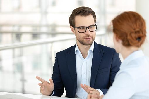 Hübsche Lächelnde Männliche Büroangestellte Im Gespräch Mit Weiblicher Kollegin Stockfoto und mehr Bilder von Abmachung