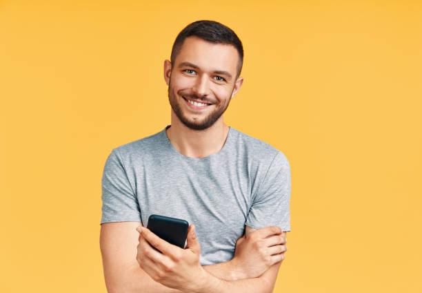 Guapo hombre sonriente sosteniendo el teléfono móvil y mirando a la cámara en el fondo amarillo del estudio - foto de stock