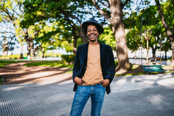 Handsome smiling man in park Portrait of handsome African smiling man in public park. medium shot stock pictures, royalty-free photos & images