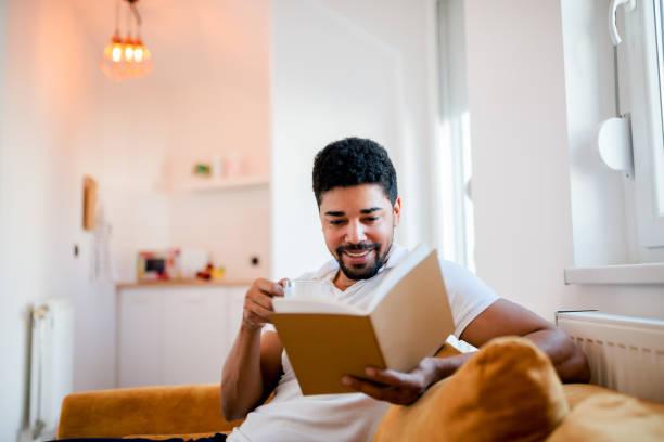 homem de sorriso considerável que lê um livro ao sentar-se no sofá. - reading - fotografias e filmes do acervo