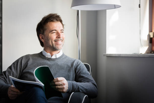 handsome smiling man reading in a sofa looking at the window - old men window imagens e fotografias de stock