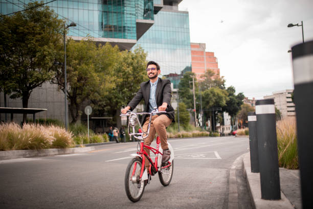 Handsome smiling man riding bike in city stock photo