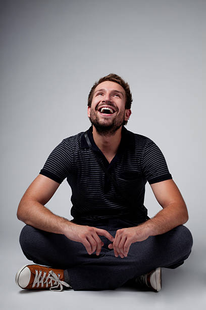 handsome smiling man sitting cross legged on the floor - sitting on floor stock photos and pictures
