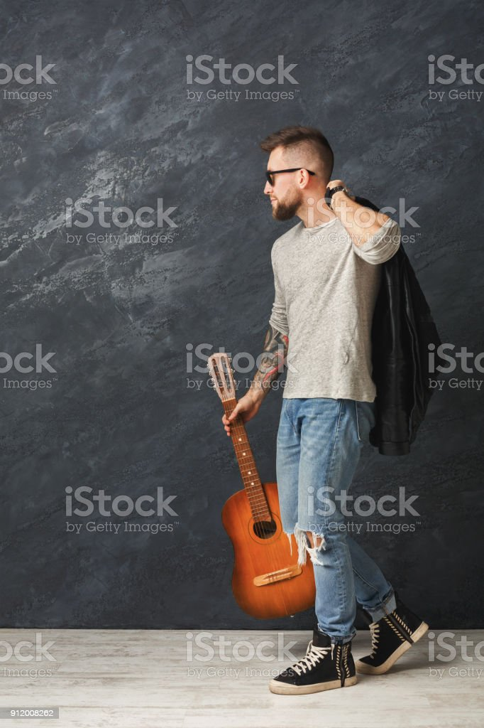 Handsome smiling man with guitar posing in studio stock photo