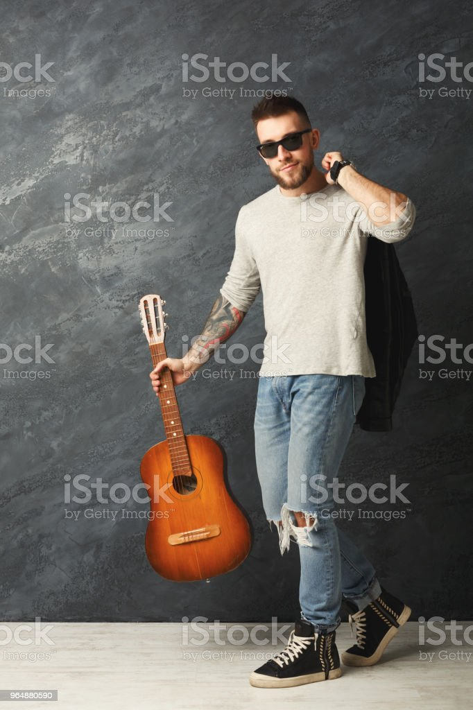 Handsome smiling man with guitar posing in studio royalty-free stock photo