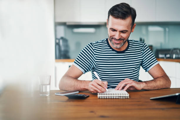 Handsome smiling man writing in notebook while managing personal finance stock photo