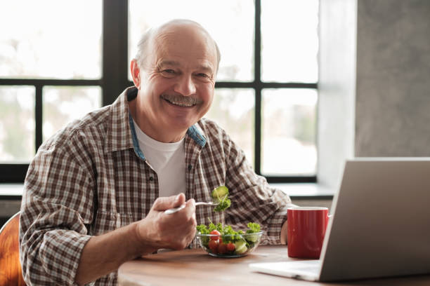 Handsome smiling mature man having healthy breakfast while sitting at kitchen stock photo