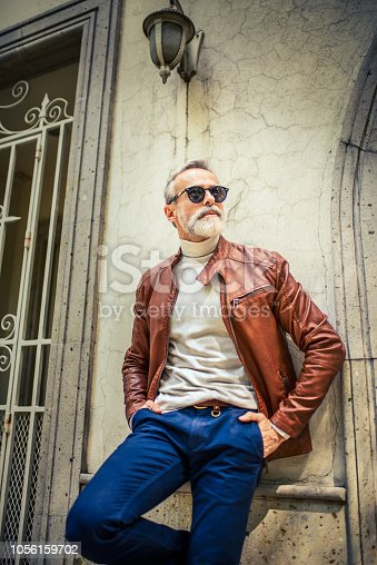 Vertical photo of a handsome mature man leaning on the wall. He is wearing leather jacket and sunglasses.
