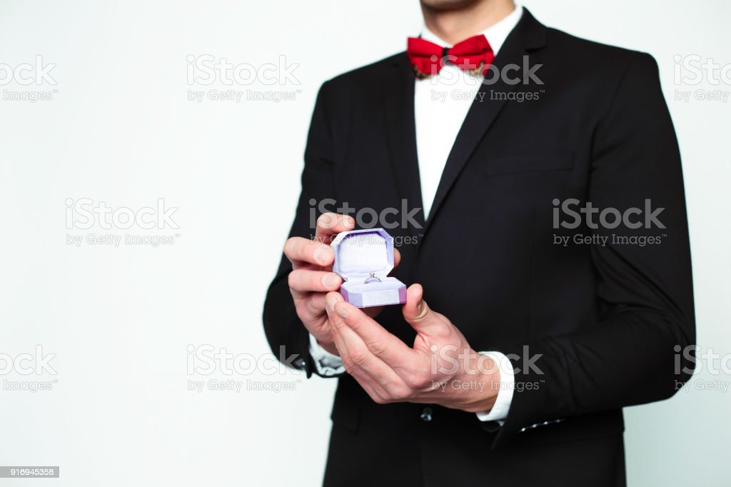 d51be7431de6 Handsome smiling modern elegant man in a official black suit and a red bow  tie is holding a box with an engagement ring and shows in camera. - Stock  image .