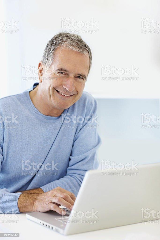 Handsome smiling senior man using a laptop stock photo