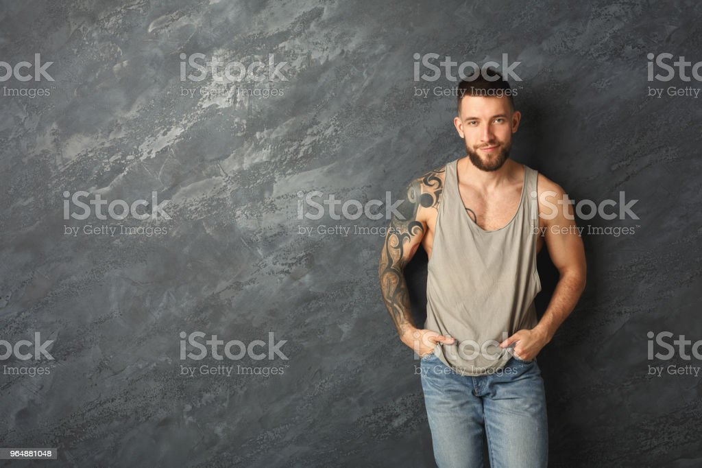 Handsome smiling tattooed man posing in studio royalty-free stock photo