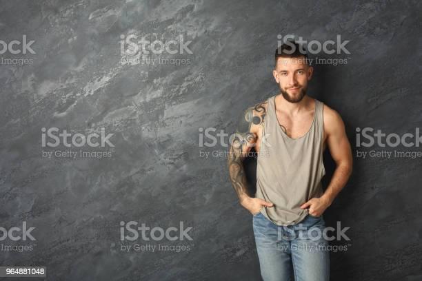 英俊的微笑紋身男子擺在演播室 照片檔及更多 一個人 照片