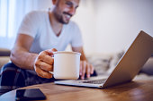 Handsome smiling unshaven caucasian man in pajamas using laptop and holding mug with coffee while sitting on sofa in living room. Morning time, selective focus on hand.