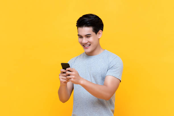 Handsome smiling young Asian man texting message on smartphone stock photo