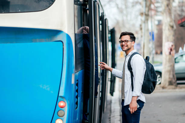 Handsome smiling young man getting into bus. stock photo