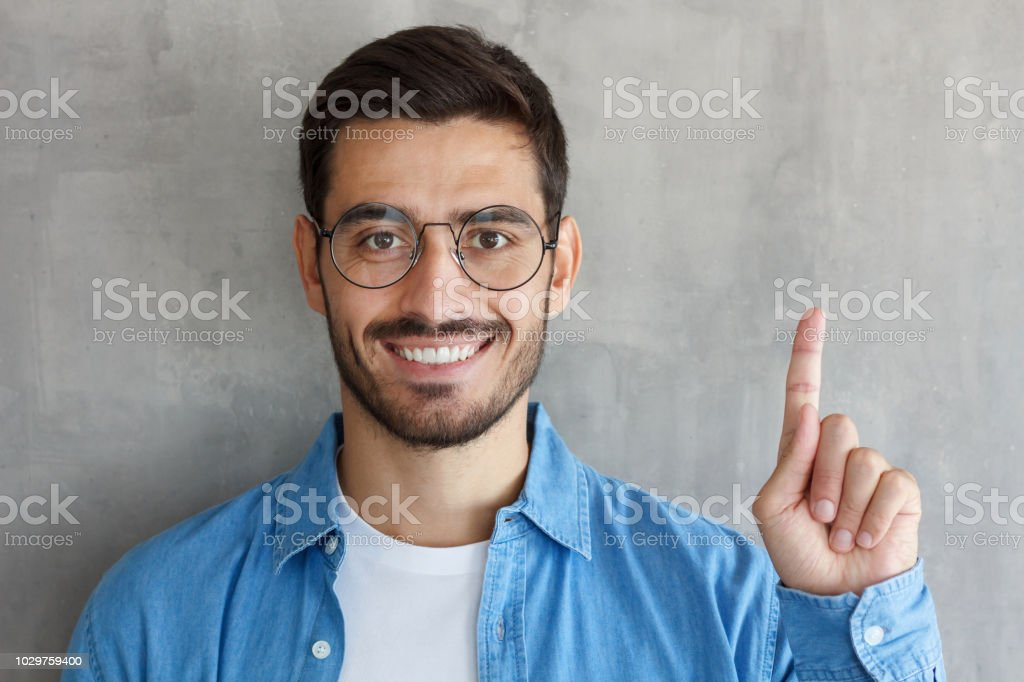 Handsome smiling young man in blue shirt adn round eyeglasses pointing up with his finger, isolated on gray textured wall stock photo