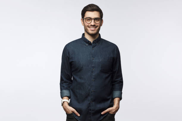 guapo joven sonriente con camisa de mezclilla casual y gafas de moda de pie aislado en fondo gris - sólo hombres jóvenes fotografías e imágenes de stock