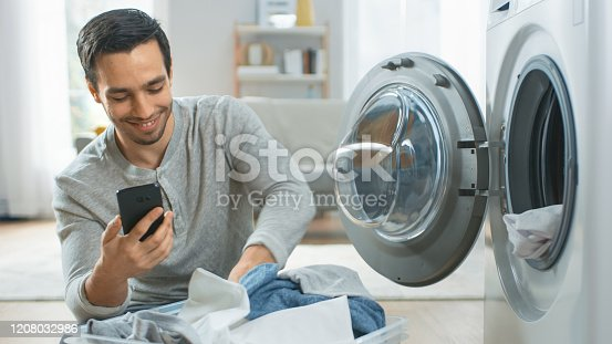 istock Handsome Smiling Young Man in Grey Jeans and Coat Sits in Front of a Washing Machine and Uses His Smartphone. He Loads Washer with Dirty Laundry. Bright and Spacious Living Room with Modern Interior. 1208032986