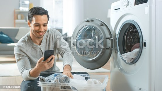 istock Handsome Smiling Young Man in Grey Jeans and Coat Sits in Front of a Washing Machine and Uses His Smartphone. He Loads Washer with Dirty Laundry. Bright and Spacious Living Room with Modern Interior. 1208033004