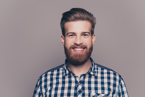 636829368 istock photo handsome smiling young man standing near  gray wall 636829300