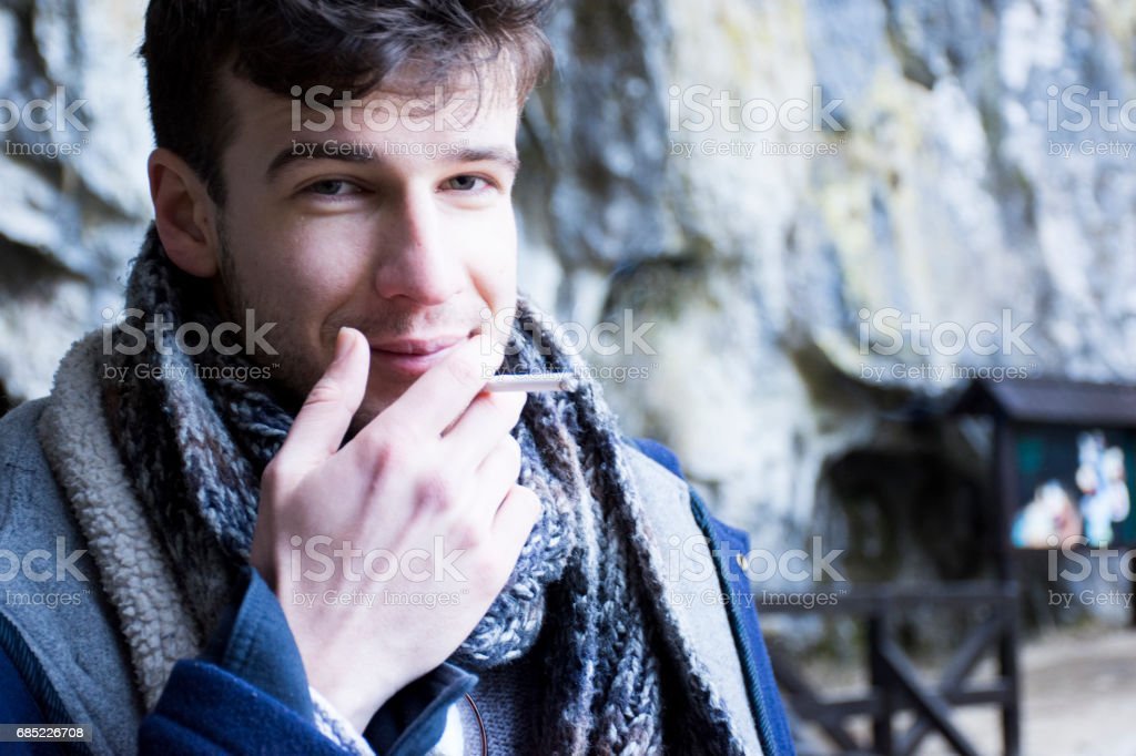 Handsome smoking young man foto de stock royalty-free
