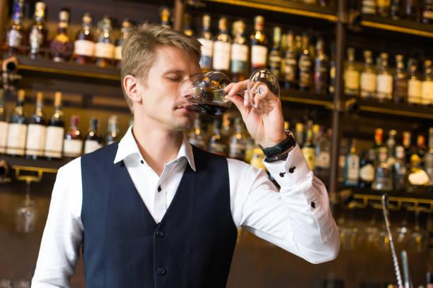 Gut aussehend Sommelier Mann duftenden Wein im Restaurant, Mann duftenden Wein im Weinglas, Mann mit Sommelier Konzept. – Foto