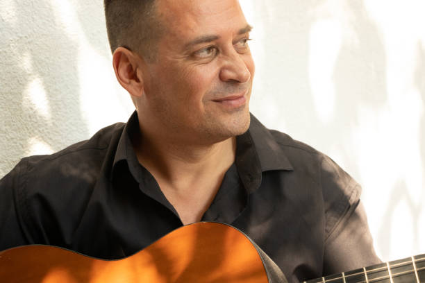A handsome Spanish man, musician playing guitar and smiling because  he is happy. stock photo