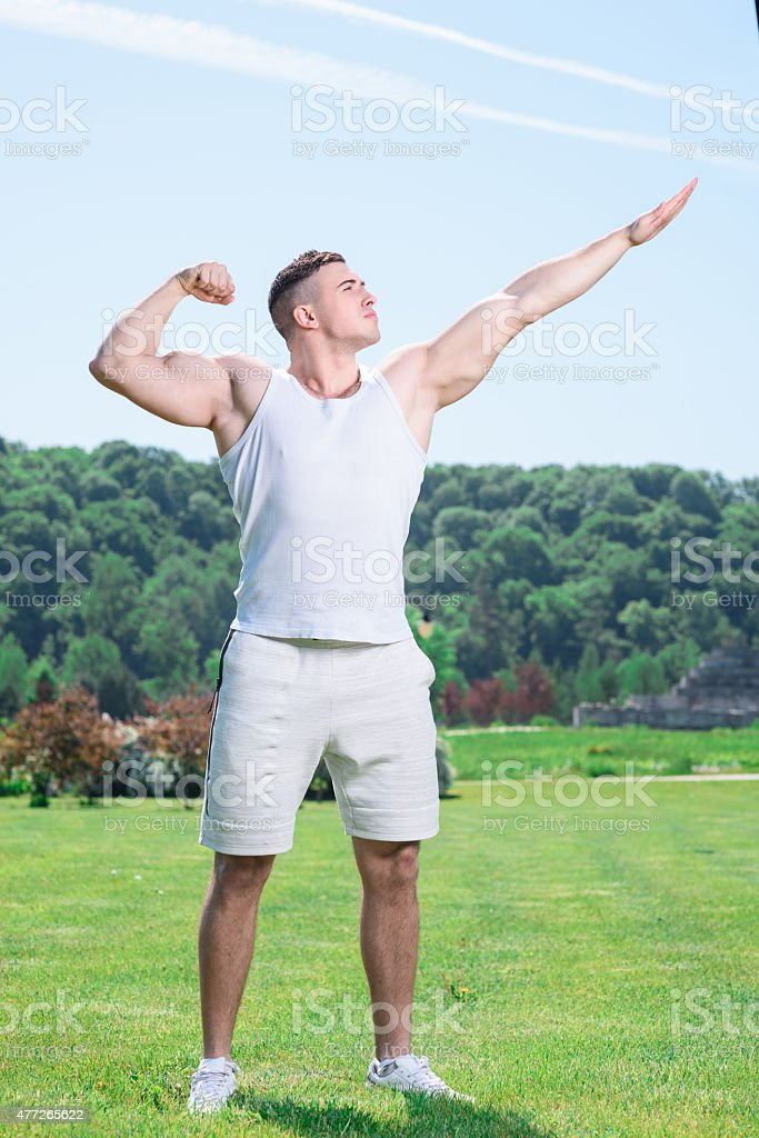 Handsome sportsman doing exercises outdoors stock photo
