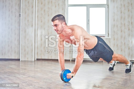 istock Handsome sportsman workout with abdominal ab roller at hall with window 1136620997