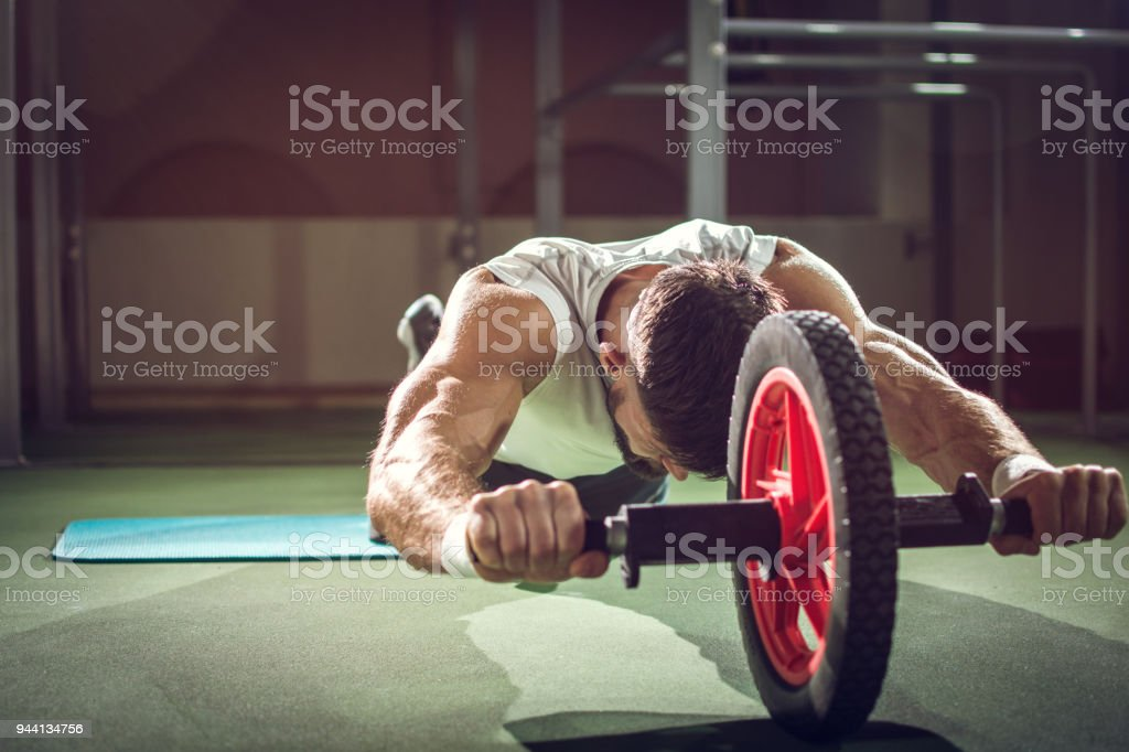 Handsome sportsman workout with abdominal roller in gym stock photo