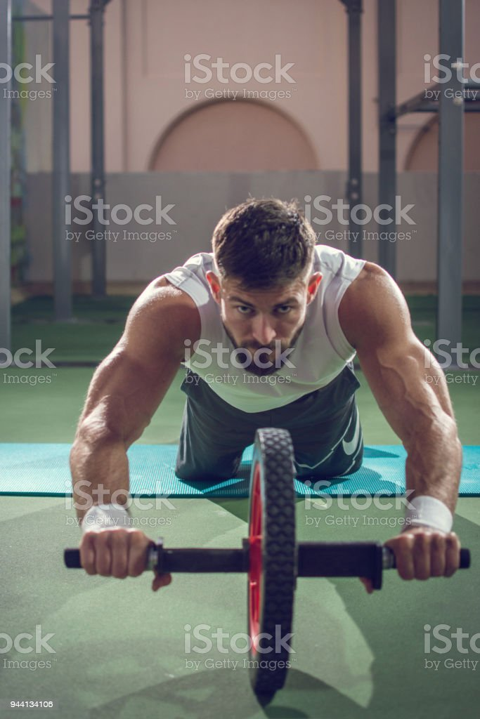 Handsome sporty man exercising with ab wheel roller and looking forward. stock photo