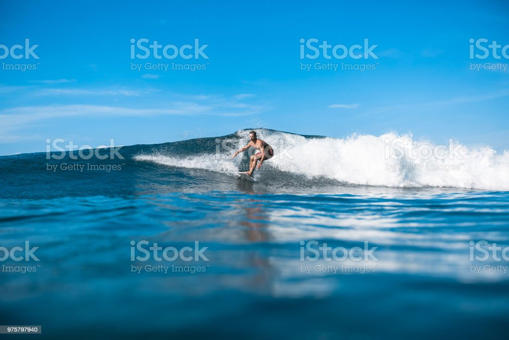 hübscher sportlicher Mann Reiten auf den Wellen an sonnigen Tag im Ozean - Lizenzfrei Abenteuer Stock-Foto
