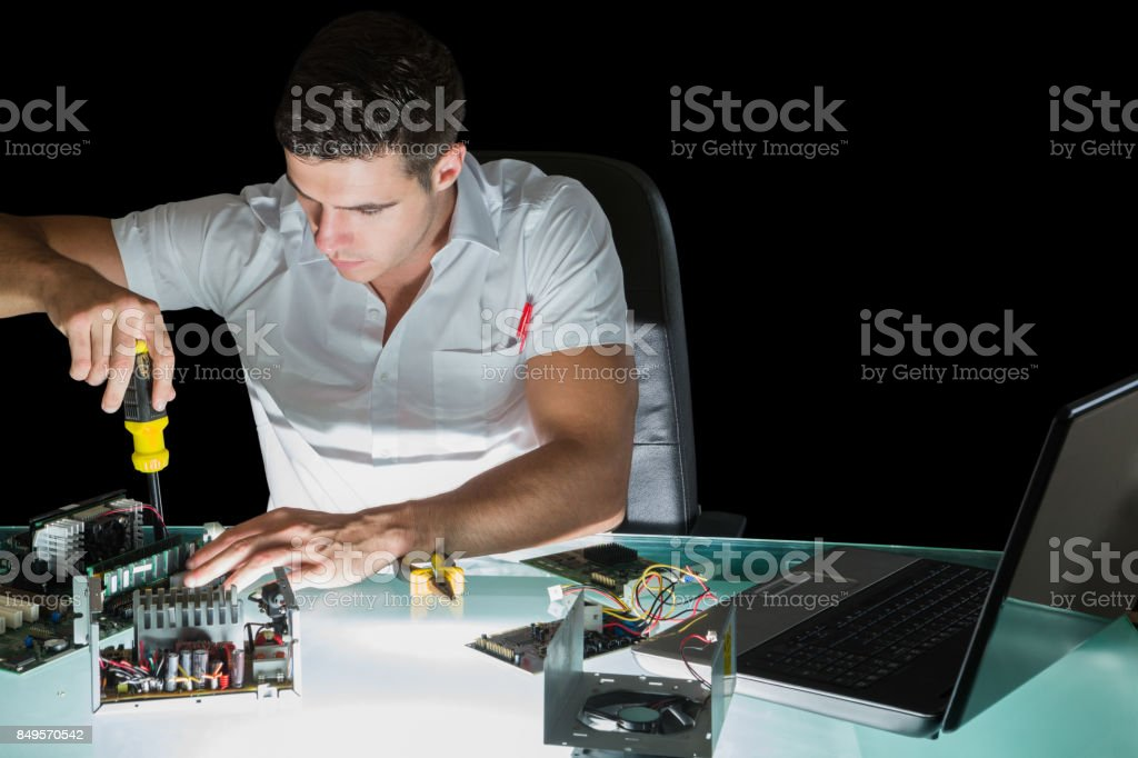 Handsome stern computer engineer working by night with screw driver...