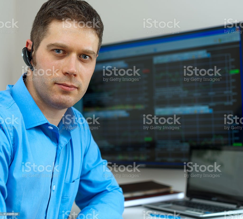 Handsome stock trader in front of computer. stock photo