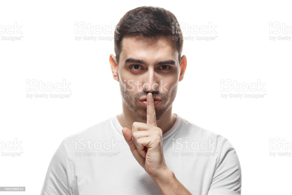 Guapo hombre estricto con shh gesto, pidiendo silencio o a estar en silencio, aislado en fondo blanco - foto de stock