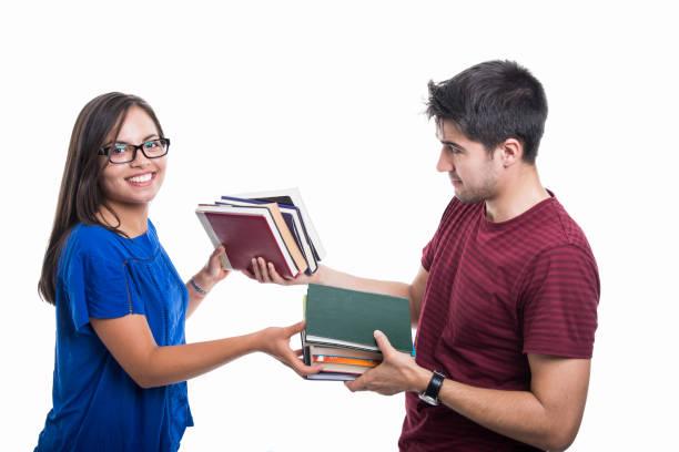 hübsche studentin paar haufen bücher austauschen - bücherbund stock-fotos und bilder