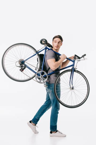 gut aussehend student hält fahrrad auf schulter isoliert auf weiss - fahrradträger stock-fotos und bilder