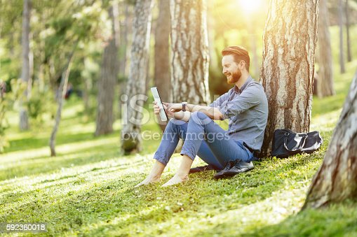 istock Handsome student reading in nature 592360018