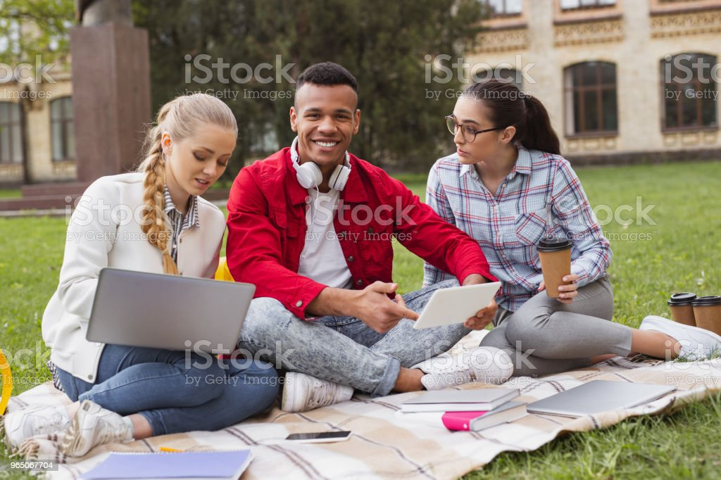 Handsome student smiling broadly spending free time with groupmates royalty-free stock photo