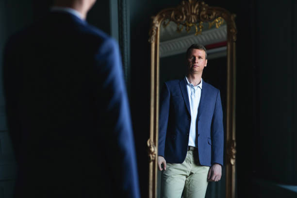 Handsome stylish man in blue jacket at home looking at mirror.