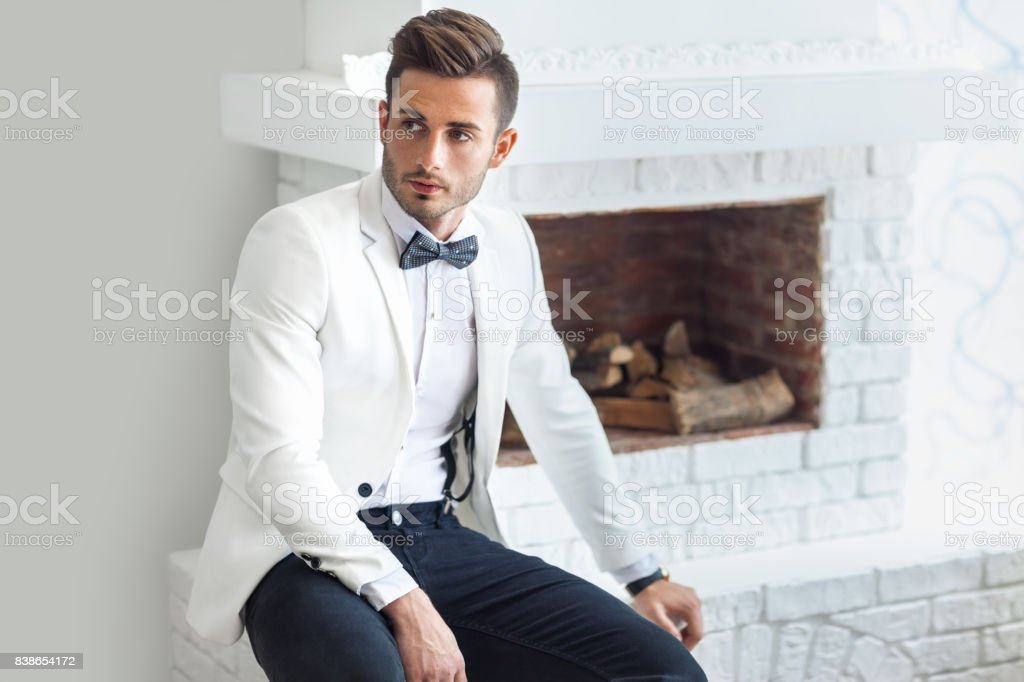 Handsome stylish man in elegant suit sitting near fireplace stock photo