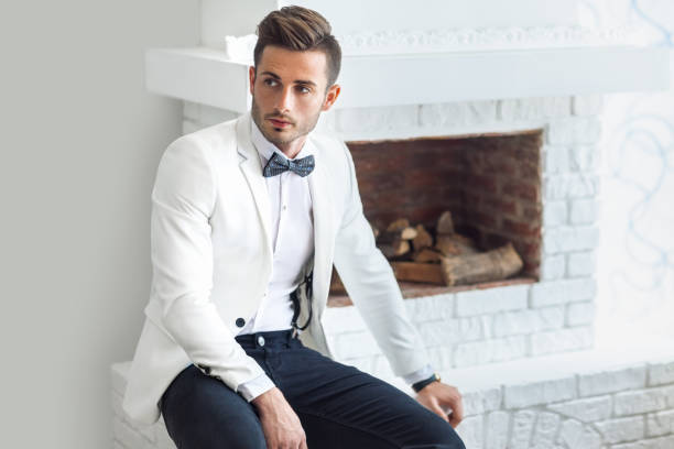 handsome stylish man in elegant suit sitting near fireplace - preppy fashion stock photos and pictures
