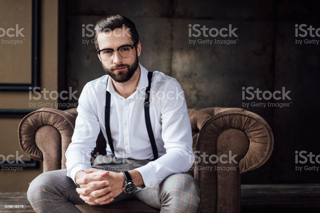 bel homme élégant dans les verres et les bretelles assis dans le fauteuil - Photo