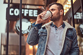 istock A handsome stylish man wearing a denim jacket with wireless headphones holding takeaway coffee outside the cafe. 1132620742